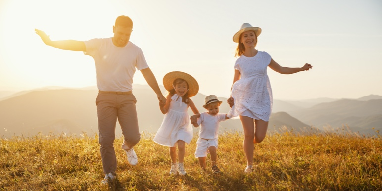 Man holding his twin daughters walking behind his son in a field of tulips. They are walking towards a weeping willow tree.